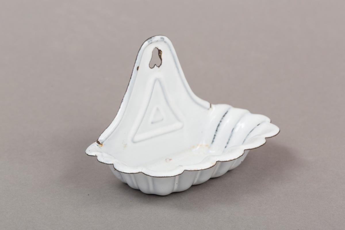 Holder til såpe. Skjellmønster i form.  I metall, emaljert. Hvit. Har tilhørende løs plate i bunn.
