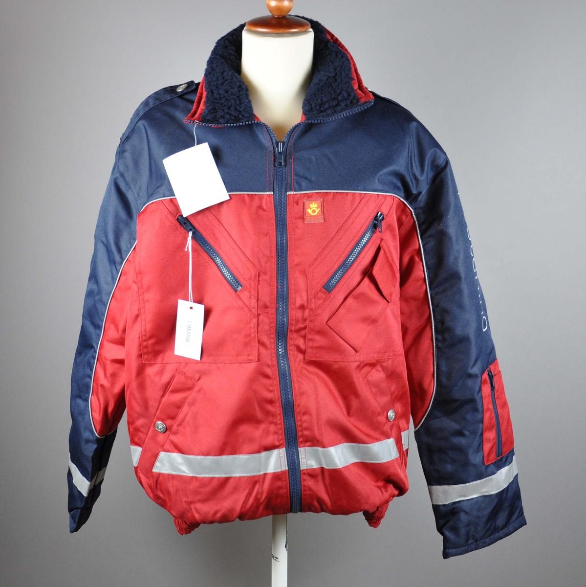 Uniformsjakke med påskrift og postlogo. Med hette og avtagbart for.Med 4 lommer og mobillomme og strikk i livet. Refleksbånd  i livet og på ermene