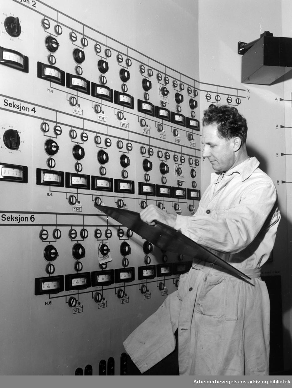 Smestad transformatorstasjon. Samkjøringssentralen. Odd Olsen foran instrumenttavla. Desember 1954