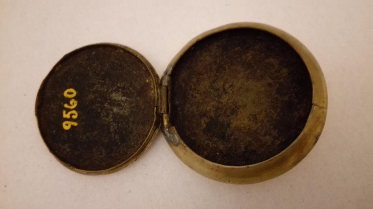 "Form: Rund og flattrykka. 1 tobaksdaase.  Rund, flattrykt tobaksdaase, diameter 7,2 cm, tykkelse 1,8 cm. Laag, i hængsler, av kobber med messing indfatning, forsirt med prikkornamenter og indgravet ""Eling"". Under bunden indgravert K.O.H. 1837.  Gave fra Anna Synnarheim, Flaam."