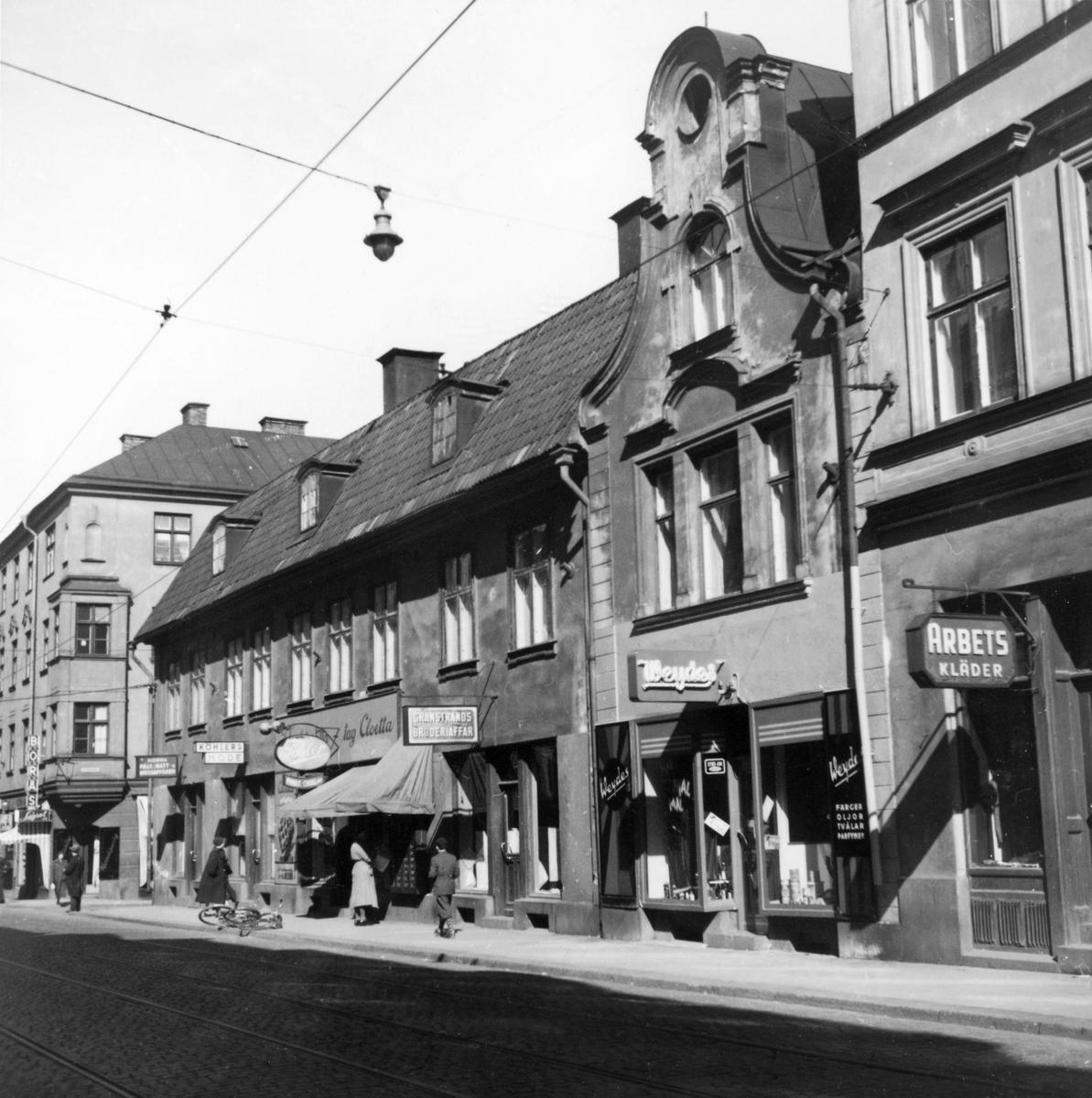 Vy mot Arnbergska gården på Kungsgatan i Norrköping. På femtiotalet var gatan en uttalad affärsgata och spårvagnen traffikerade även denna del av staden. På bilden ses sett urval av de affärer som låg här så som Toblers Frukt och Choklad, Köhlers Mode, Norra Päls - Hatt- & Mössaffären, Granstrands broderiaffär, Weydes, med mera.