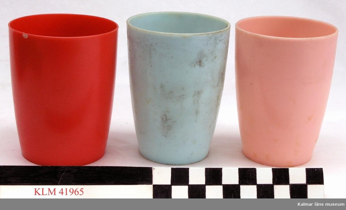 KLM 41965 Mugg, 3 st, plast. Rak sida något vidgande sig uppåt. Tre muggar med snarlikt utseende, en ljusblå, en rosa och en röd, den röda något större. Kan ha använts som dryckesmugg eller tandborstningsmugg.
