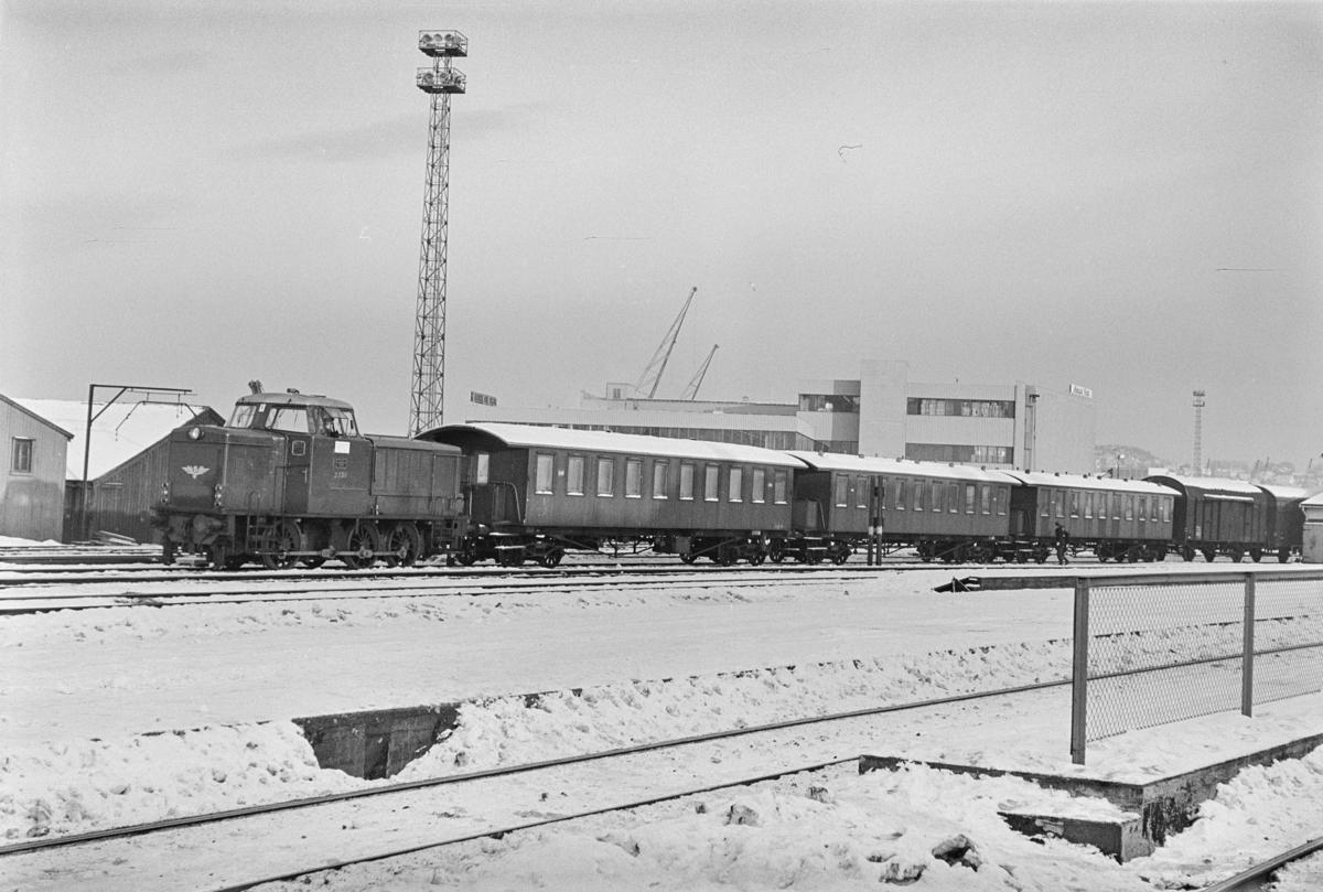"""Utrangerte personvogner type Bo4a, såkalte """"sportsvogner"""", på Trondheim stasjon. Vognene trekkes av diesellokomotiv type Di 2 nr. 830."""