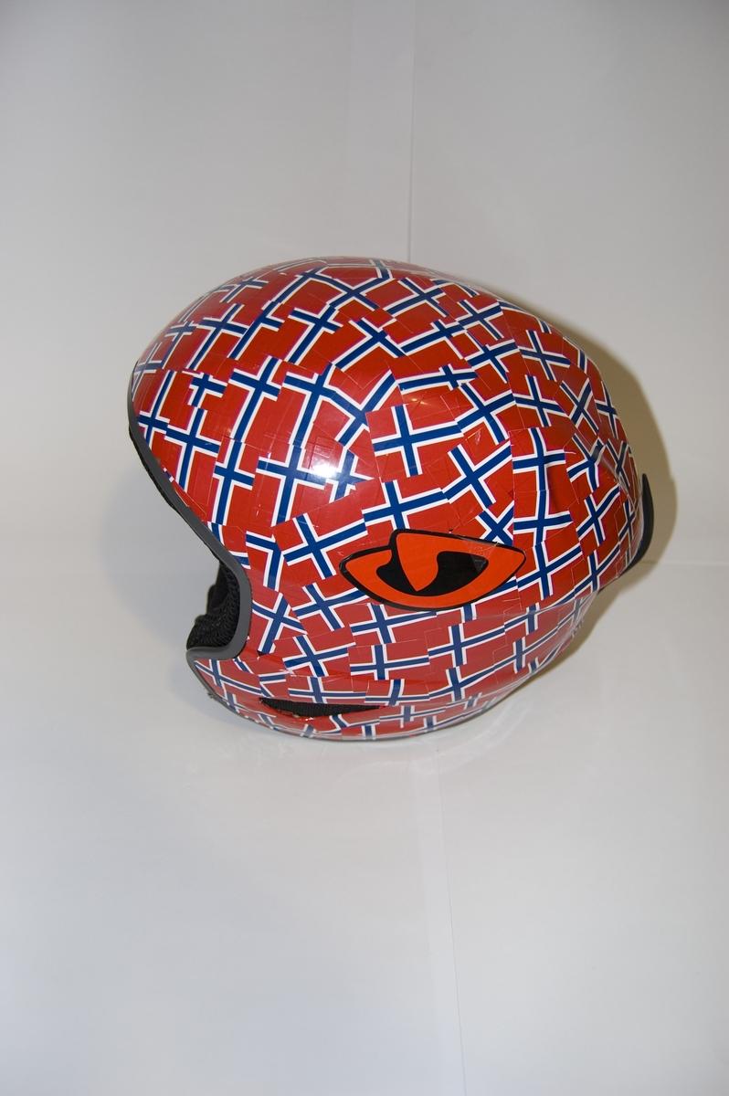Alpinhjelm med påklistert merker med motiv av det norske flagget. Stramme- og tilpasningsanordning bak på hjelmen.