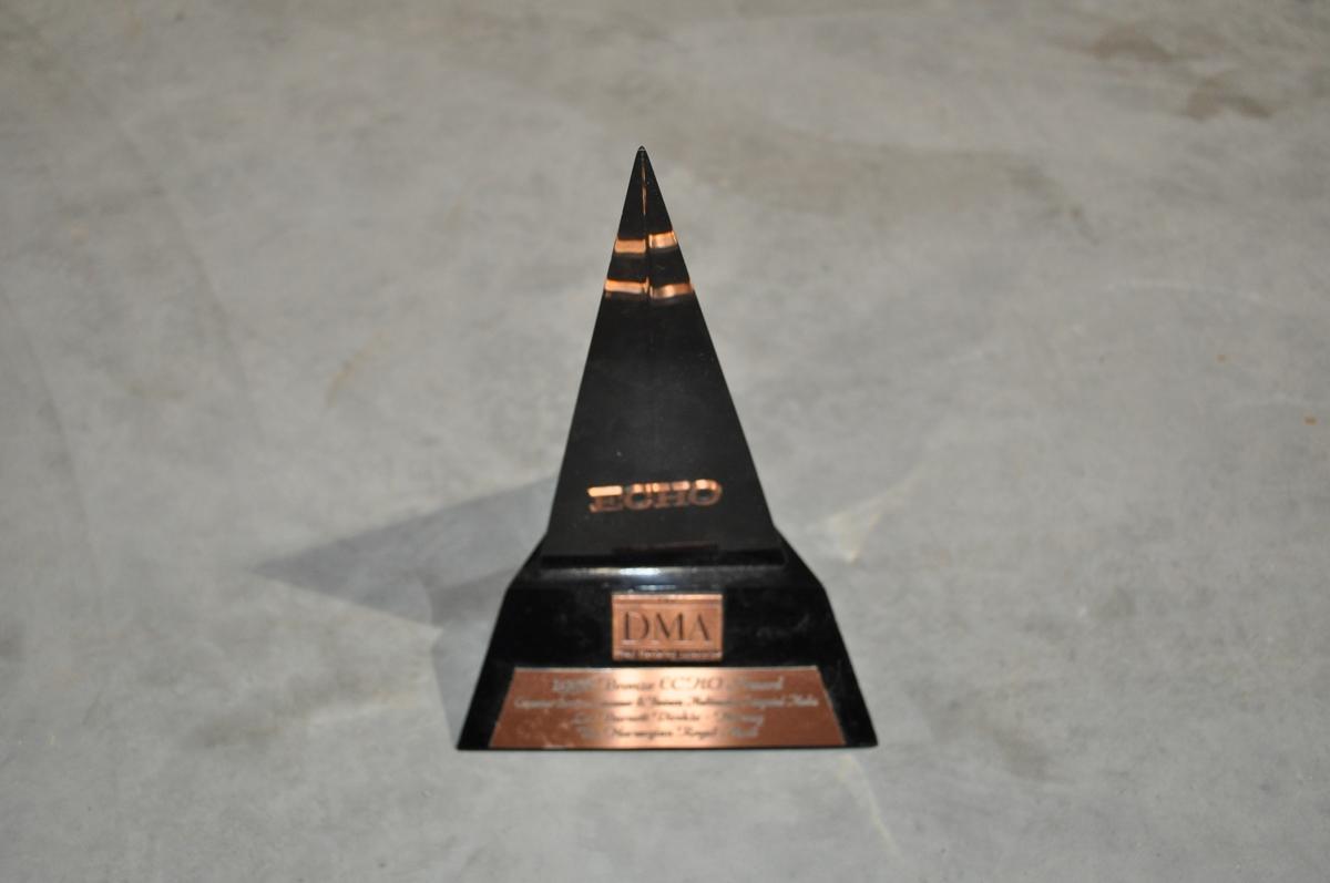 Pyramideformet i svart og blanh hardplast med innskrift: THE DMA Direct Market Assosiation 1998 Bronze ECHO Award