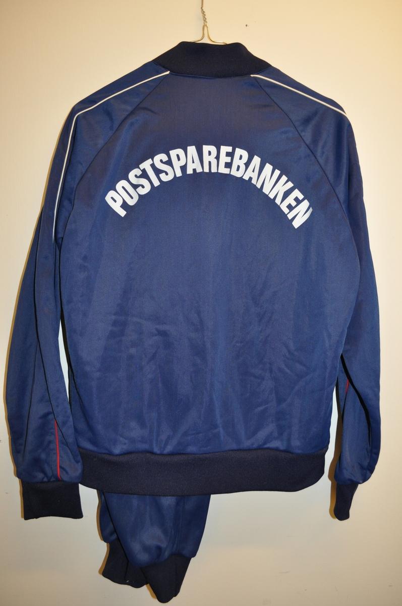 """Treningsdress (bukse og jakke) med Postbankens logo og ordet """"Sportsmann"""", samt ordet """"Postsparebanken"""" på ryggen. Jakken har to stikklommer.  Størrelse 48."""