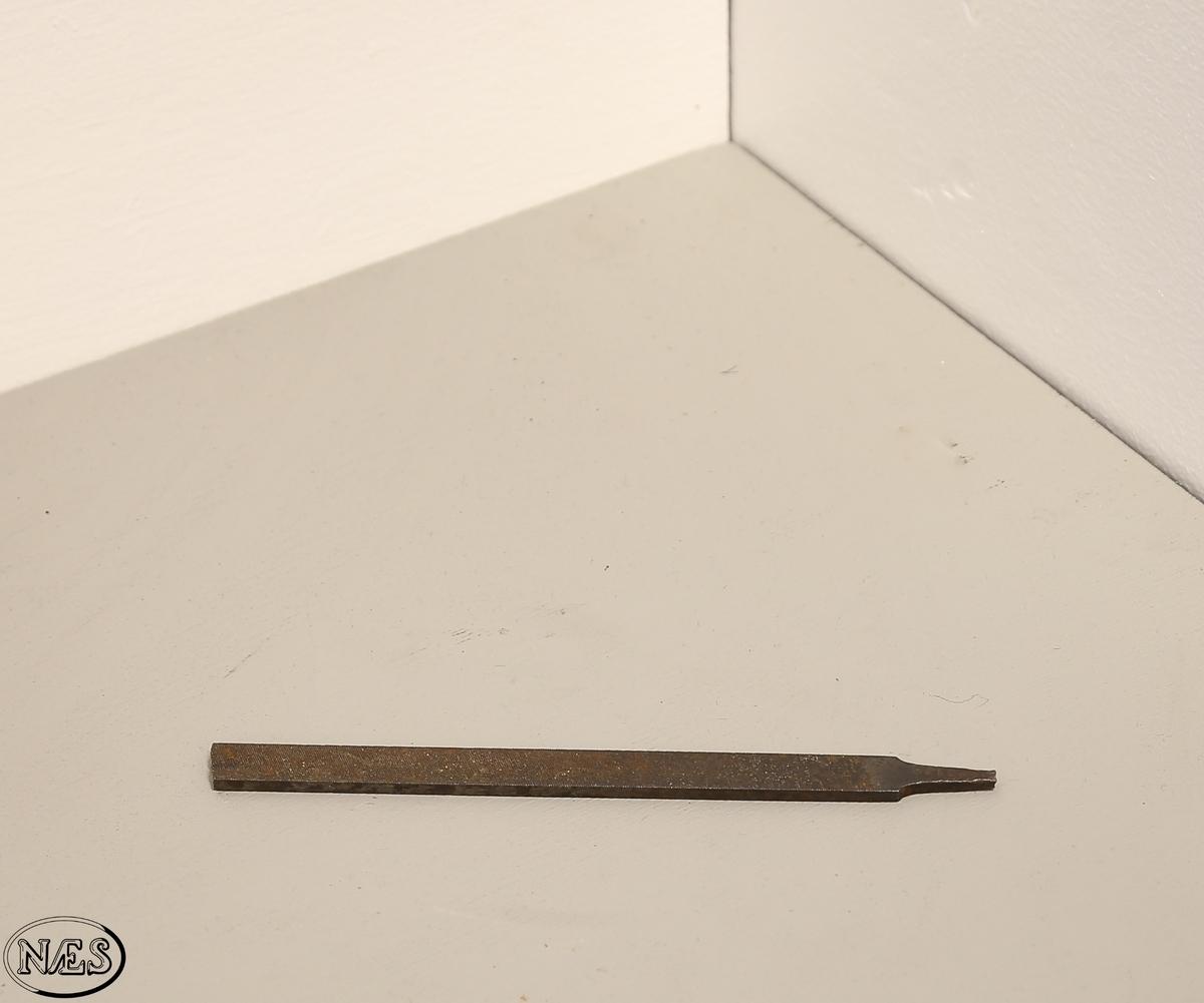 Filen har et flatt tversnitt med diagonale rifler/ spor på begge flatene. Filen er knekt i begge ender og har ikke skaft.