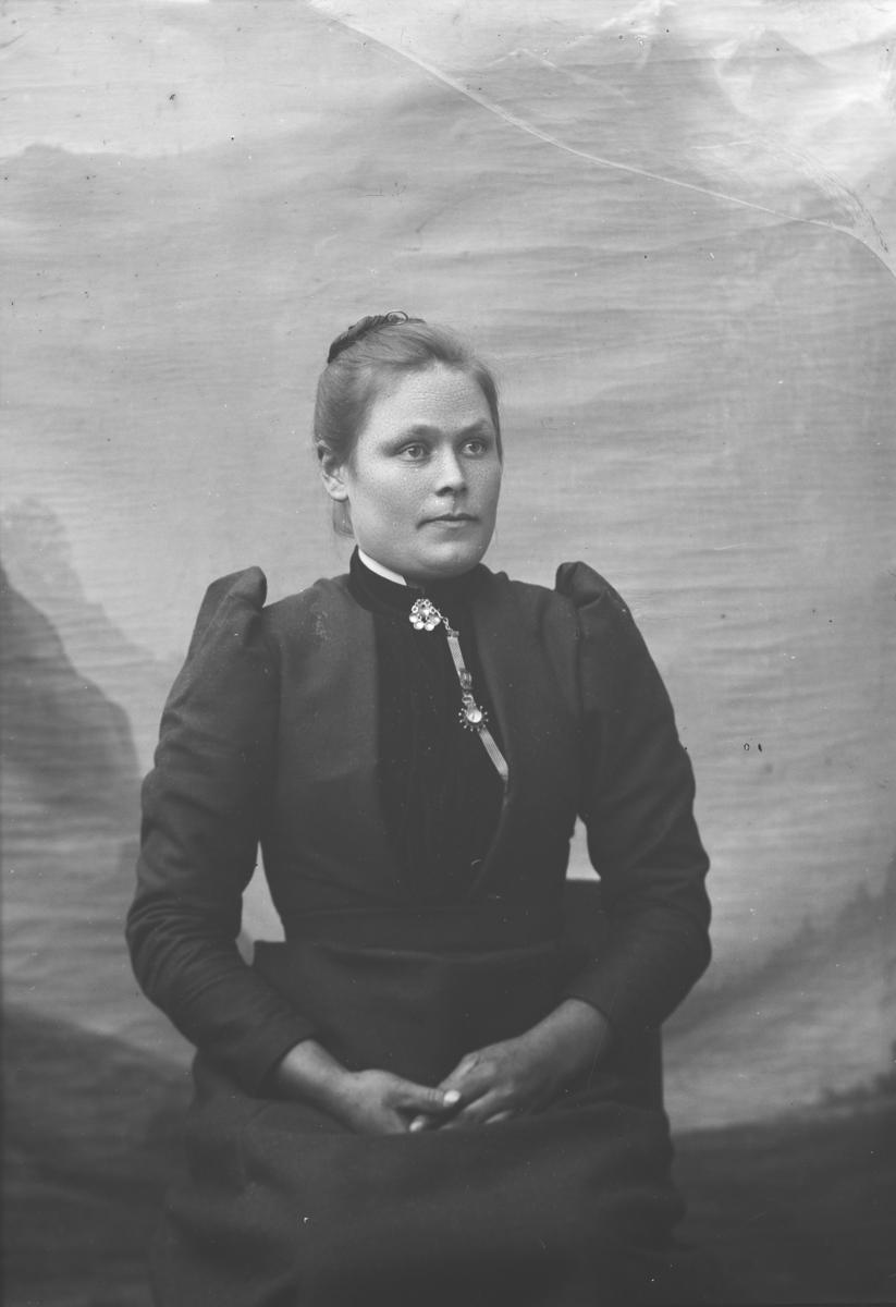 Portrett, kvinne sitter på stol, brystbilde