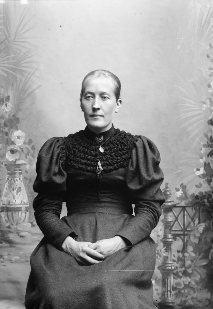 Portrett, kvinne sitter på stol, brystbilde.