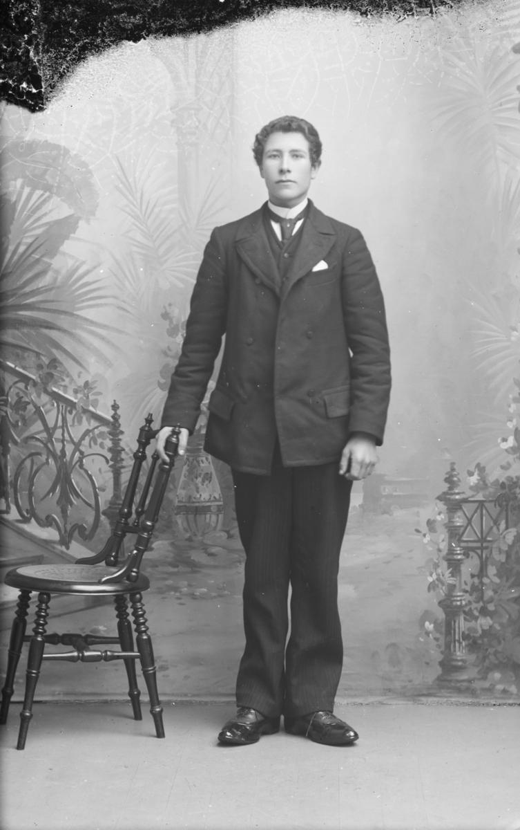 Portrett, mann står ved stol, helfigur