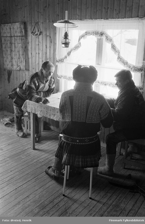 """Postfører Mathis Mathisen Buljo, bedre kjent som """"Post-Mathis"""" i samiske kretser, i samtale med to av sine postkunder inne på kjøkkenet i Bávtajohka. Den ene kunden er Josef Iversen Sara (Iver Jofset).  Fotograf Henrik Ørsteds bilder er tatt langs den 30 mil lange postruta som strakk seg fra Mieronjavre poståpneri til Náhpolsáiva, videre til Bavtajohka, innover til øvre Anárjohka nasjonalpark som grenser til Finland – og ruta dekket nærmere 30 reindriftsenheter. Ørsted fulgte «Post-Mathis», Mathis Mathisen Buljo som dekket et imponerende område med omtrent 30.000 dyr og reingjetere som stadig var ute i terrenget og i forflytning. Dette var landets lengste postrute og postlevering under krevende vær- og føreforhold var beregnet til 2 dager. Bildene gir et unikt innblikk i samisk reindriftskultur på 1970-tallet. Fotograf Henrik Ørsted har donert ca. 1800 negativer og lysbilder til Finnmark Fylkesbibliotek i 2010."""