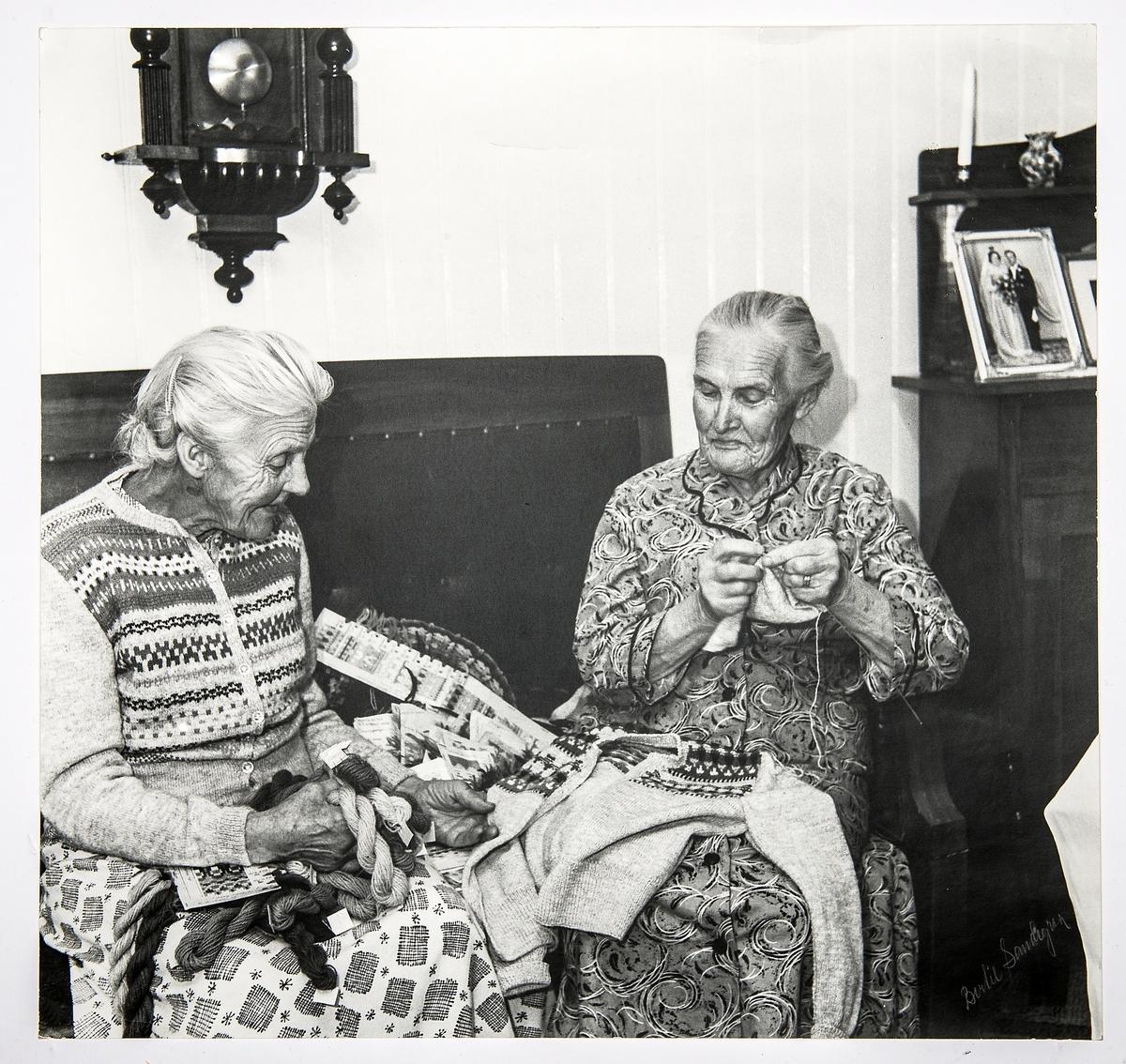 Alma Olsson och Maria Johansson sitter bredvid varandra i en soffa i Marias finrum. Alma har en kofta från Bohus Stickning, Blå Randen - formgivare Anna-Lisa Mannheimer Lunn - och Maria stickar på en kofta till samma företag. Mellan sig har de garner och mönsterdiagram till olika mönster som ingick i Bohus Sticknings kollektioner. Båda stickade åt Bohus Stickning, bilden är tagen inför Marias 80-årsdag och publicerades i Strömstads tidning 16 november 1957.