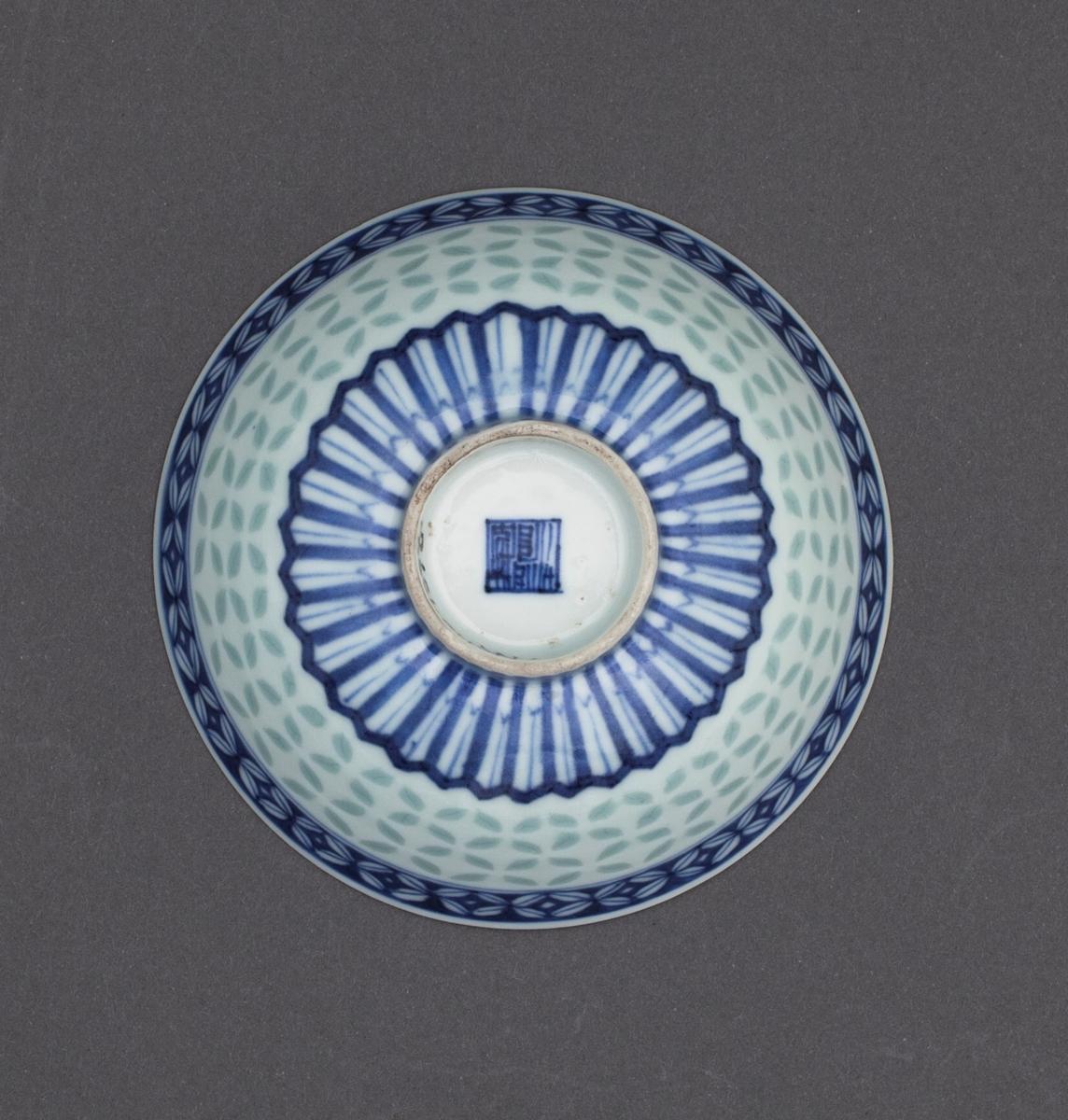 Bollen har et gjennomgående og transparent riskornmønster på midten av cavetto. Glasuren i dette mønsteret er grågrønt. Langs munningskanten på utsiden av cavetto finner vi en dekorkant med riskornmønster i koboltblå underglasur. På undersiden av cavetto finner vi en dekorkant av lotuspanel i koboltblå underglasur. På Innsiden av cavetto finner vi langs munningskanten en dekorkant med arabesk i koboltblå underglasur. I speilet på bollen finner vi «wufu:» de fem velsignelser (representert av fem flaggermus) som kretser rundt en stilisert utgave av «shou» (tegnet for langt liv). Gruppen er omrammet av to konsentriske sirkler. Alt i koboltblå underglasur. Rundt foten finner vi to konsentriseke sirkler i coboltblå underglasur. Under bunnen av bollen i håndmalt, koboltblå underglasur, Qianlongs keiserlige segl.  Lokket har nøyaktig det samme dekorprogrammet som bollen, bortsett fra at knoppen ikke er dekorert.