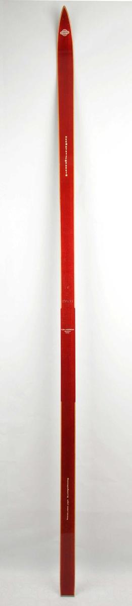 Langrennski laga av tre. Raudlakkera overflate, trekvite sidekantar. Intersport-emblem i framtupp. Metallbeslag på baktupp.