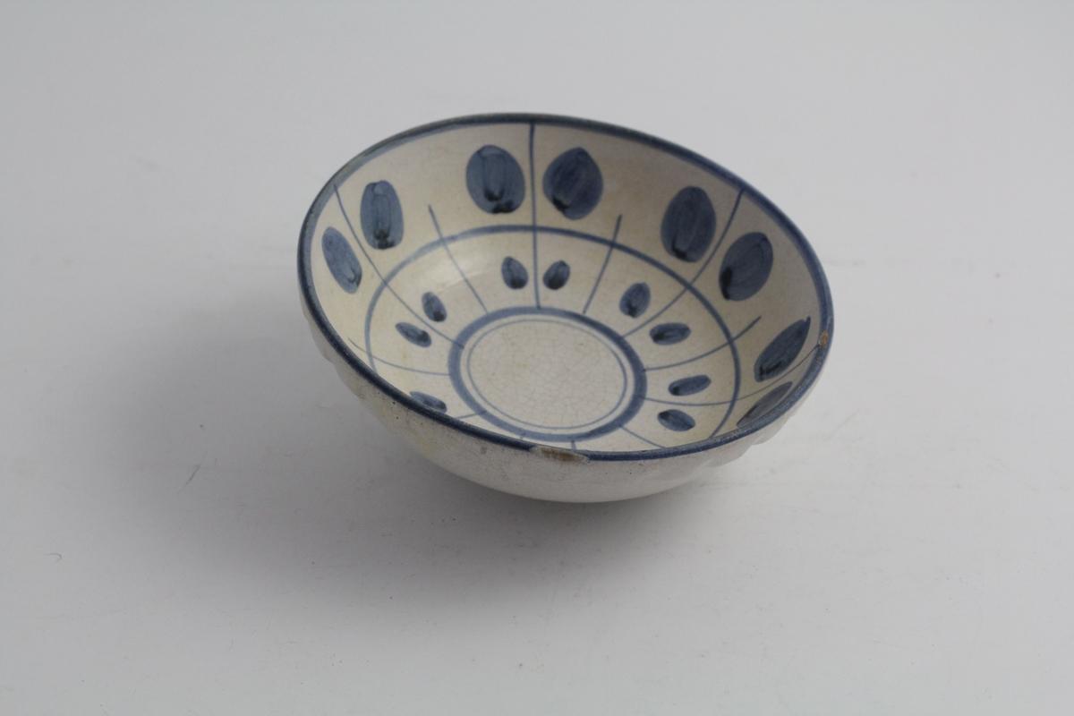 Rund, dyp skål i keramikk. Grå glasur med blå dekor. Håndmalt med streker og fylte rundinger.