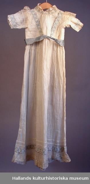 d5dca93dd493 Hellång dopdräkt av vit bomullsvoall med infällda spets- och sidenband.  Knytband i ryggen. Photo: Hallands kulturhistoriska museum