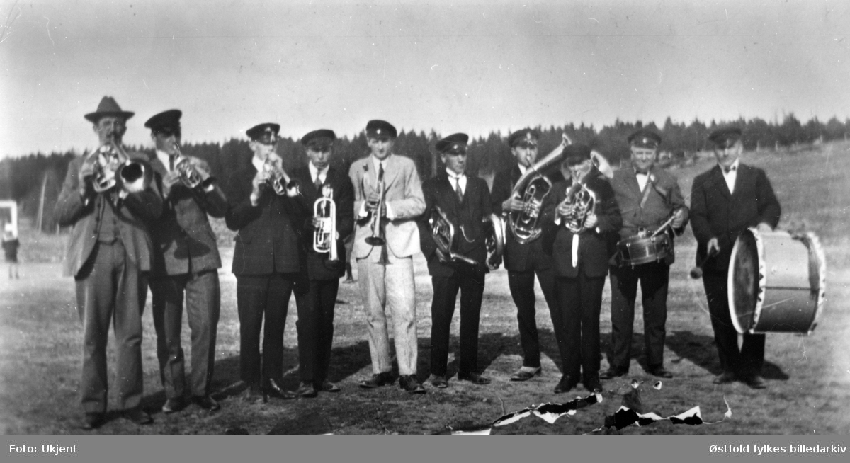 Spydebergmusikken i Spydeberg i 1927.  Spydebergmusikken spilte til dans, på fotballkamper eller der det var behov. Spydebergmusikken eksisterte fra 1923- 1933.   Fra venstre:  Engebrett Grini, Sverre Nilsen, Leif Espenes, Gunnar Ruud, Osvald Grini, Johannes Mamelund, NN, Tore Grini, Alf Helle, Sigurd Jensen.