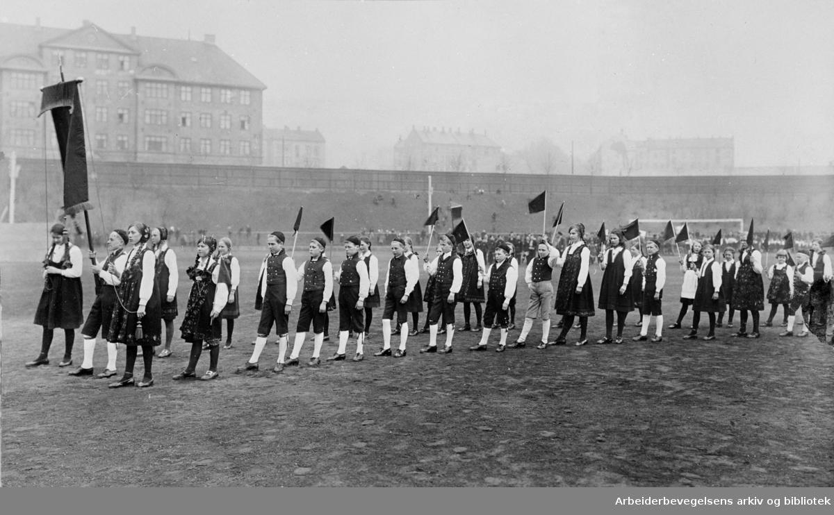 1. mai 1924, barnestevne på Dæhlenengen stadion. Medlemmer av Oslo Fremtids dansarring marsjerer inn på stadion.