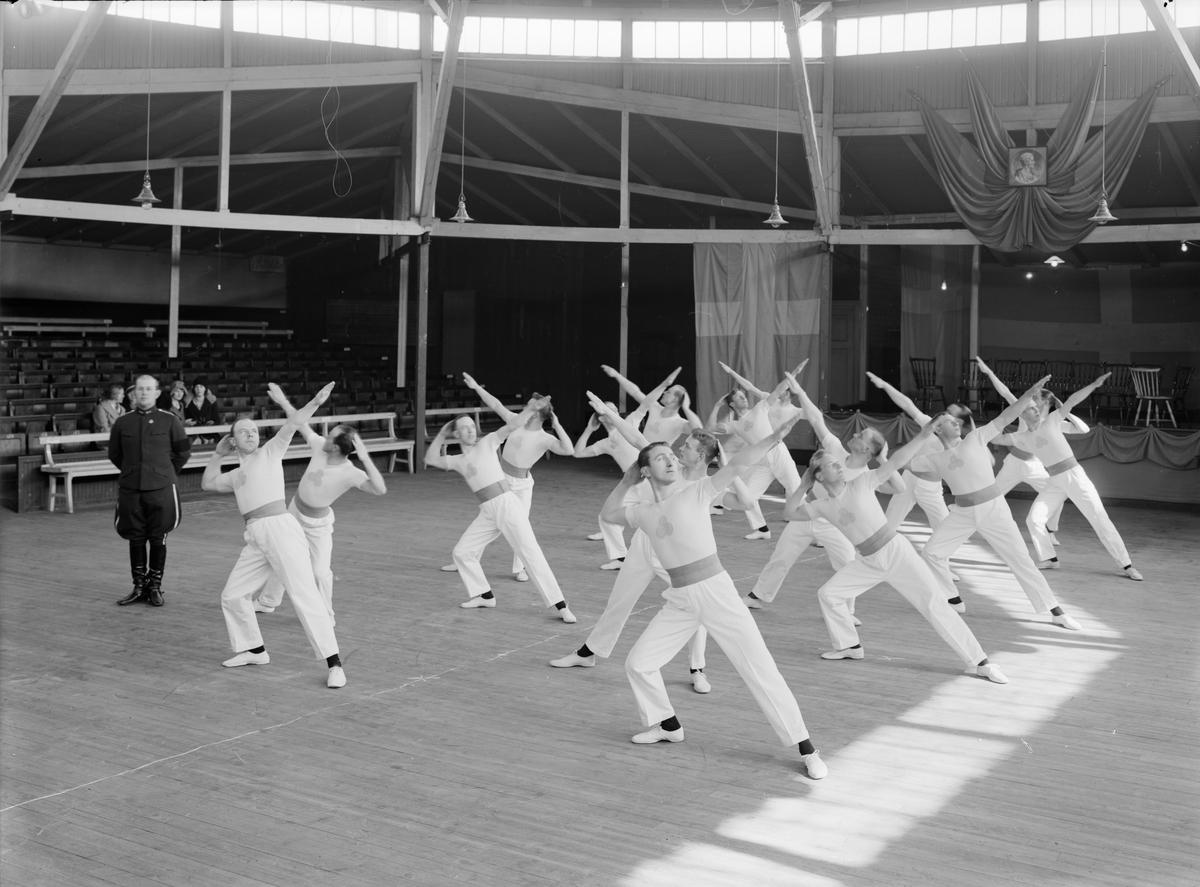 Linköpings gymnastikförenings manliga elittrupp visar upp sina färdigheter. Platsen är Cirkus på Platensgatan.