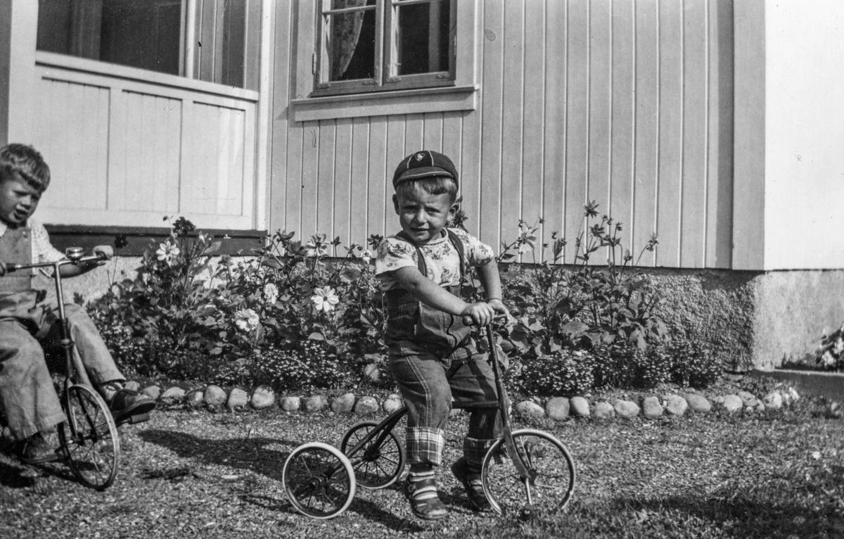Barn, 2 ukjente gutter på trehjulsykkel.