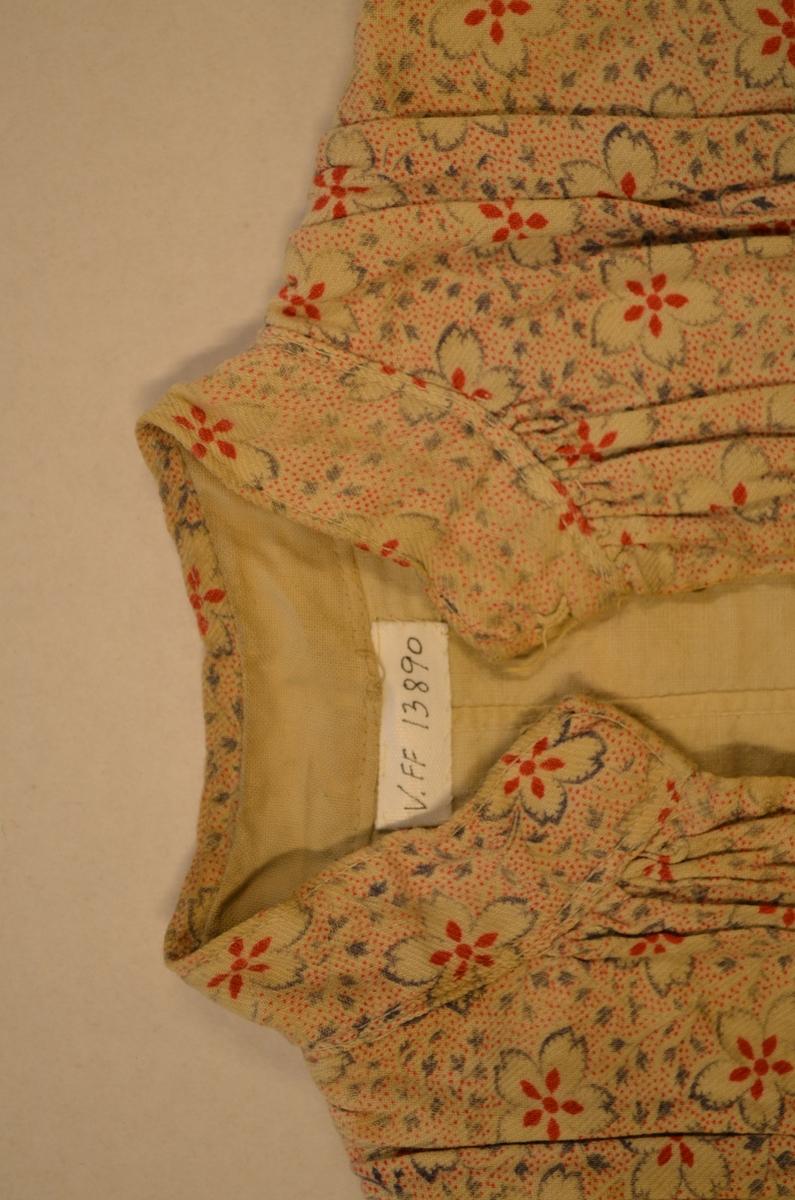 Kjoleliv for jente i kypertvove bomullstøy med blomemotiv. Fóra med lerret. Opning framme med 9 hekter og 9 krokar på innsida, smal linning i halsen. Sløyfe i same tøyet midt framme. Ermane er avrevne, 20 cm er att.