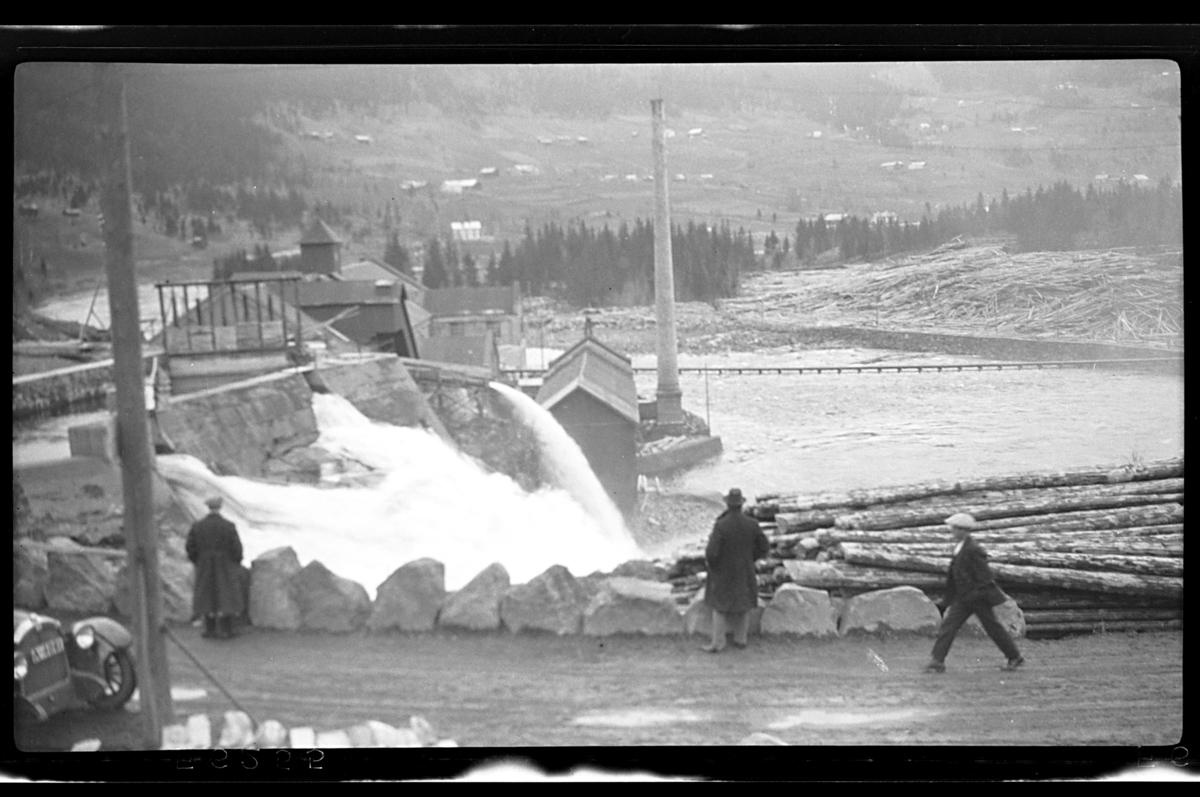 Tømmer ligger på begge sider av en elv og ant. sagbruk ligger ved siden av. Fotografert 1926.