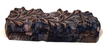 Mönsterstämpel av trä med utskuret mönster.