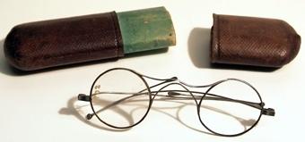 Glasögon med tillhörande utdragsfodral av papp, klätt i brunt skinn.