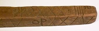 Fyrkantig trästav med inskurna tecken och initialer.