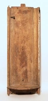 Skåpet har snedställda sidor mot ett rektangulärt bakstycke. Sidorna är fästade med tränaror. Rester av röd och vit färg finns. En smidd spik som tjänat som infästning av skulpturen sitter kvar i skåpets bakstycke och en annan smidd spik har tjänat som upphägning av skåpet. Skåpet saknar figur.