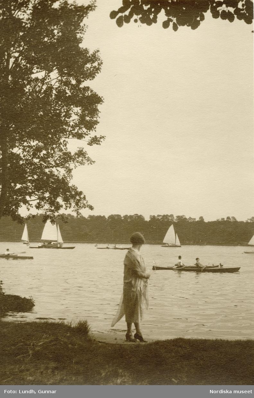 Tyskland. Kvinna vid strandkanten vid en sjö. I bakgrunden rodd- och segelbåtar.