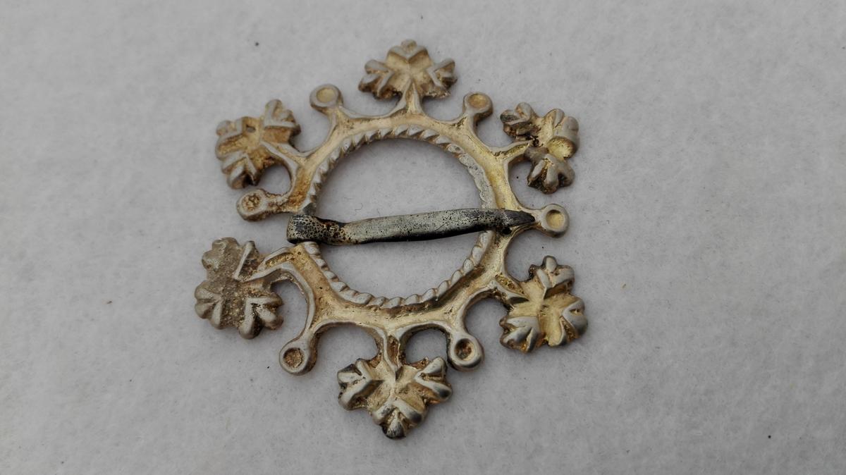 Sølje av sølv.  Liten støpt sølje med naal, forsiden forgyldt. Fra Hafslo. Kjøpt av Jens Skavl, Leikanger.