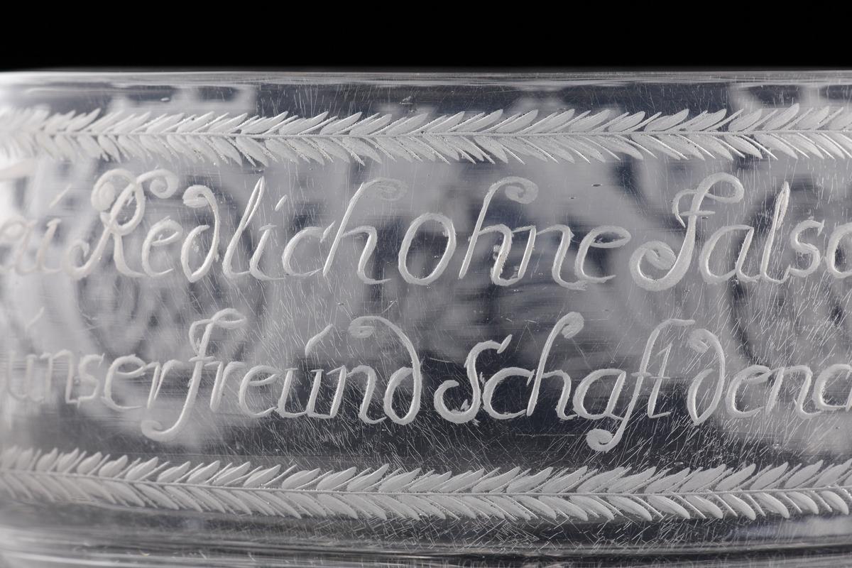 """Skål av glas med hänklar.  Graverad dekor med två spegelmonogram under friherrekronor och tysk text: """"Treu Redlich ohne Falsch und Schein, Soll unser FreundSchaft dench Spruch Sein"""".  Vilar på tre kulfötter."""