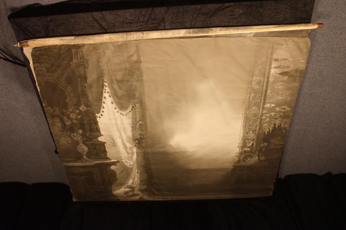 Gardin nytta som bakgrunn i fotoatelier. Motiv gardin, pidestall og blomsteroppsats