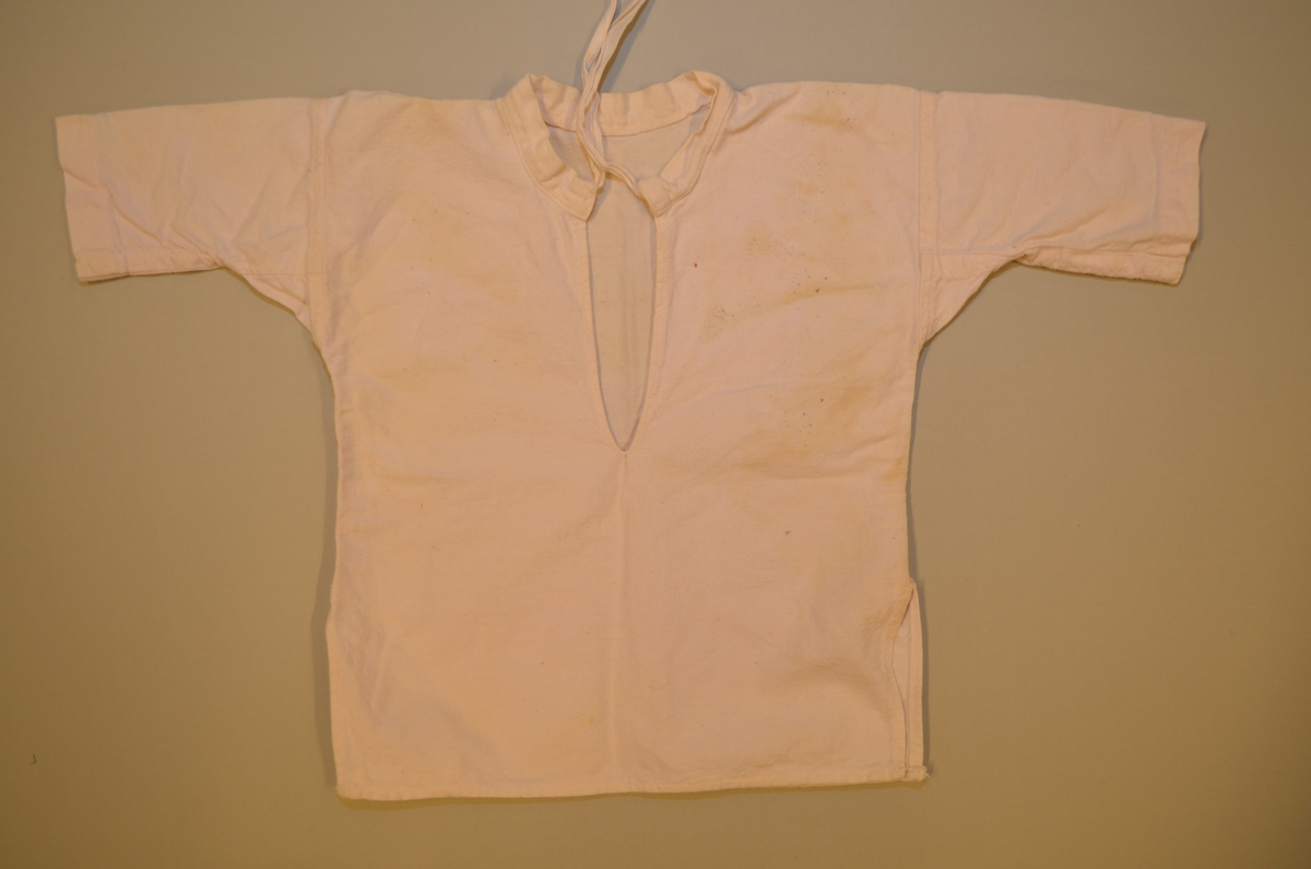 Barne skjorte i kvit bomullslerret med knyteband i halsen. primærsnitt med splittar midt framme og i sidene. Smal linning i halsen. Maskinsydd.