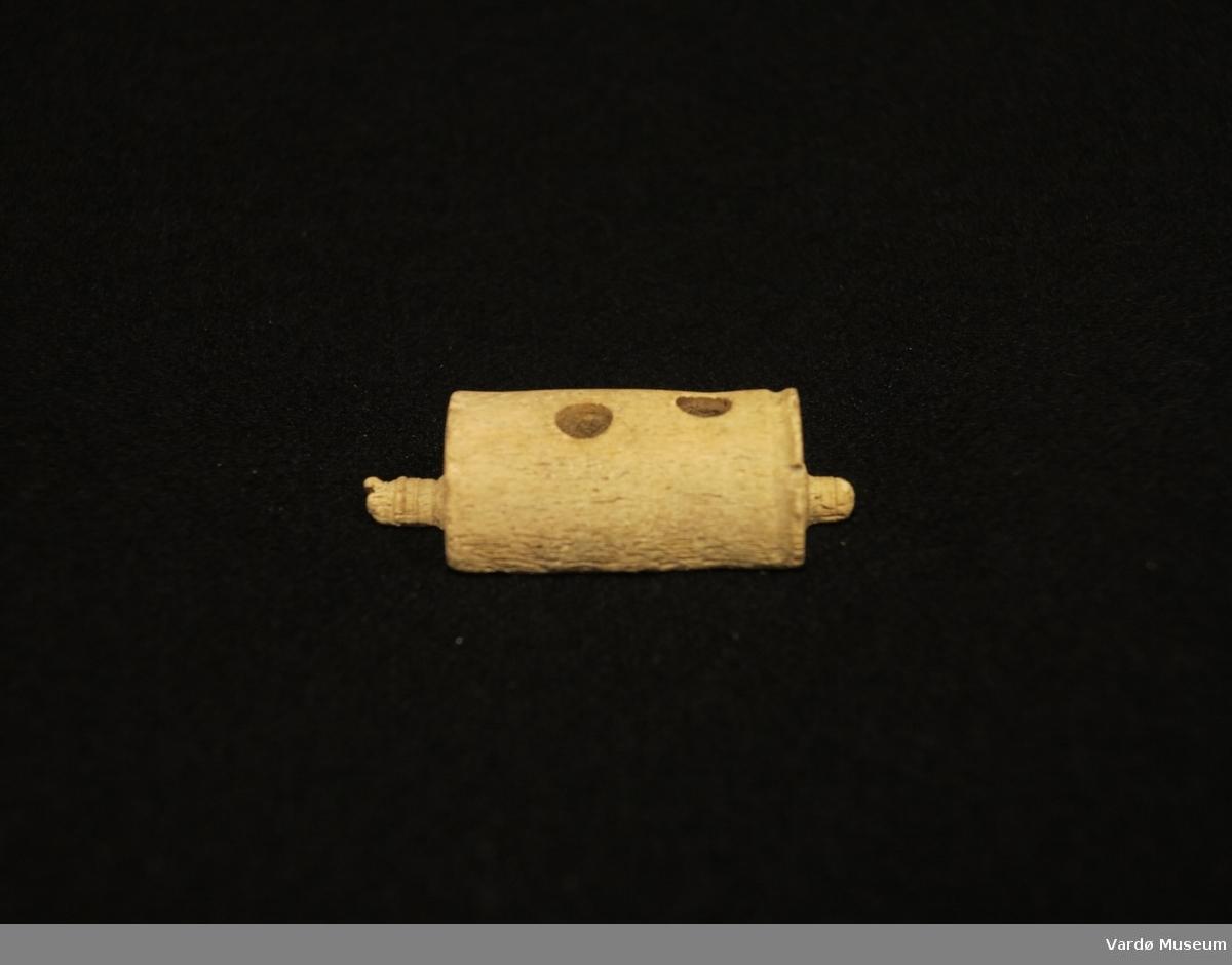 Halvsylindriske og porøs gjenstand med to hull og noen slitasjmerker. Gjenstand er en tredjedel av hele vabeinrullen.