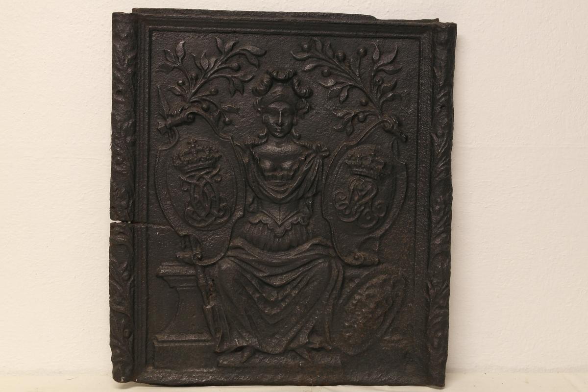 Ovnsplate i støpt jern. Motivet er en brynjekledd, sittende kvinneskikkelse (Minerva) som er flankert av to kronede monogrammer (Kong Christian VI - 1730-1746 - og dronning Sophie Magdalene)