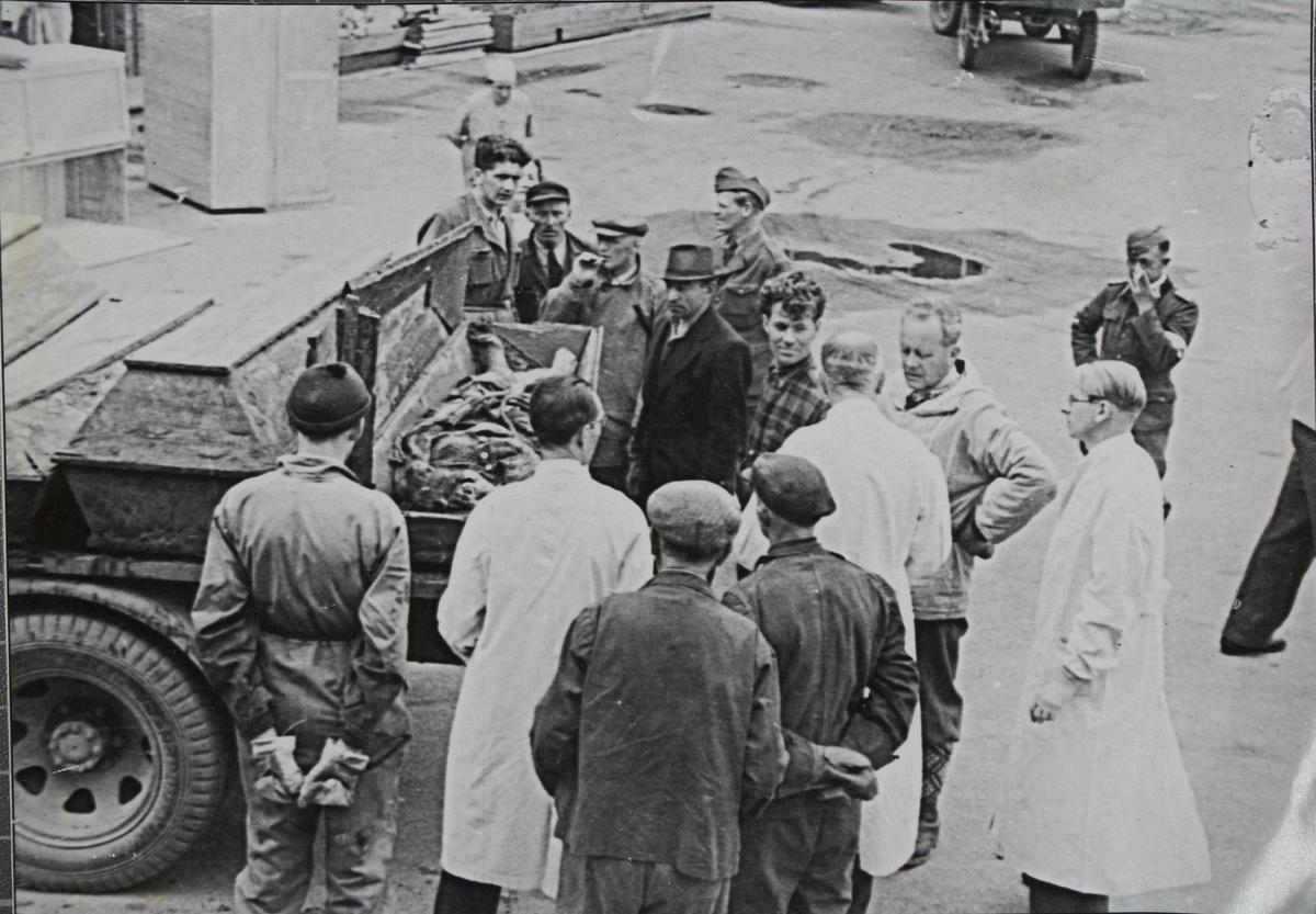 Åpen likkiste på et lasteplan, med en gruppe menn rundt. Noen i hvite frakker, noen sivilkledte og noen i militæruniform.