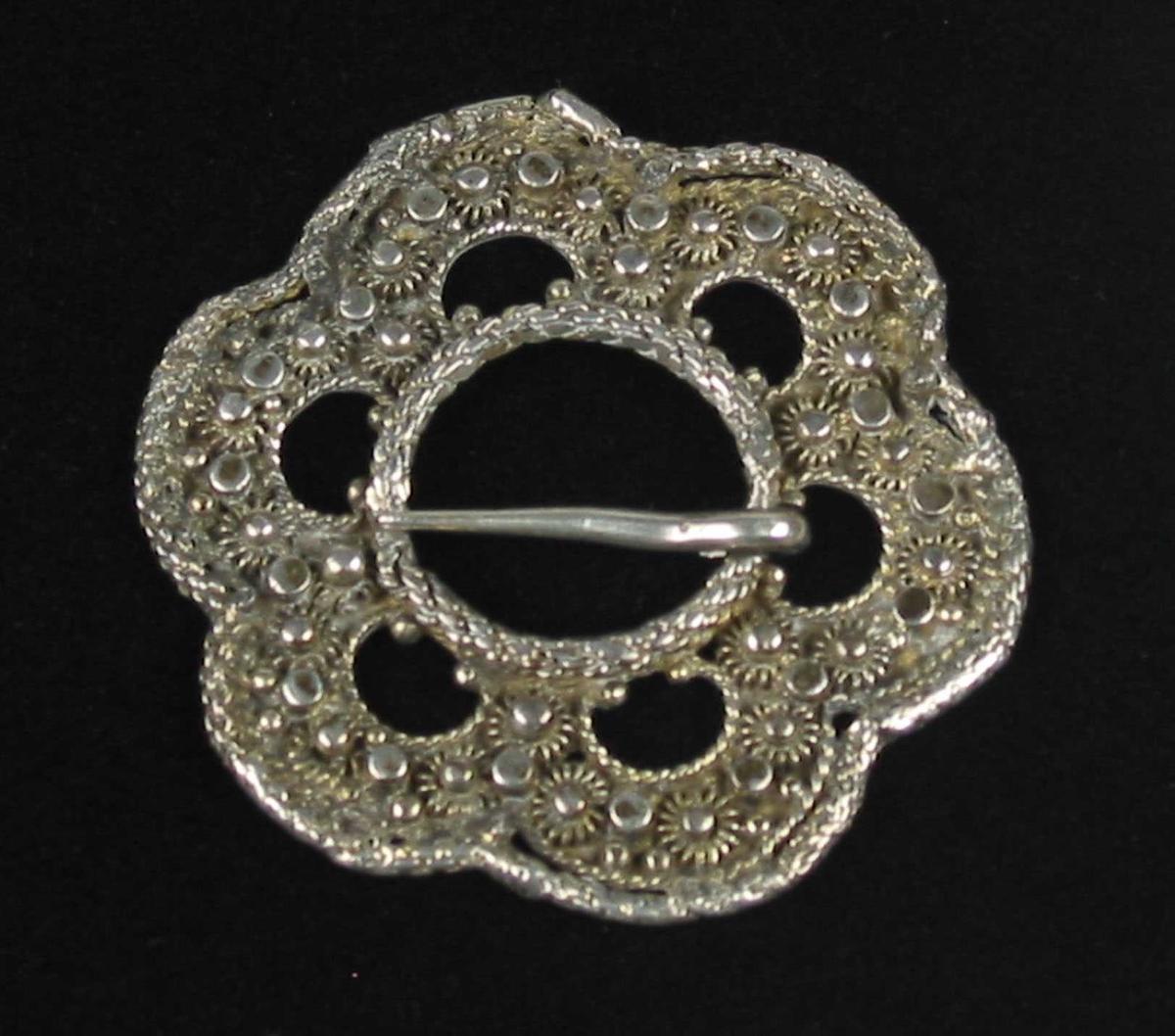 Lita forgylt rosettformet slangesølje i sølv. Sølja består av seks segmenter påsatt knupper og perlekruser.  Segmentene er kantet med tvinnetrådsbånd.Tornringen og kanten ytterst er formet av en rørtrådsring. Tornringen er noe opphøyet. Sølja har ingen synlige stempler.