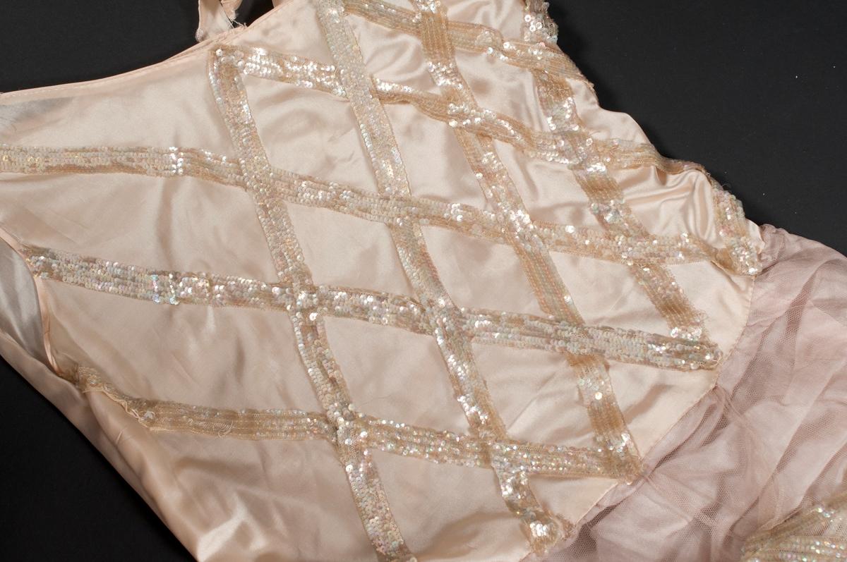 Rosa klänning av siden med kjol i två lager, siden och tyll. Liv dekorerat med paljettband som bildar ett rombmöster. Den övre tyllkjol dekorerad med pakjettband i mönster och avslutas med sidenkantade volanger. Pocher isydda under kjolen i klänningens sidor. Snedskuren halrsinging, på ena sidan ett samare axelband. Knäppning med tryckknappar till vänster på klänningens bakstycke. Paljetterna är pärlemorskimmrande.