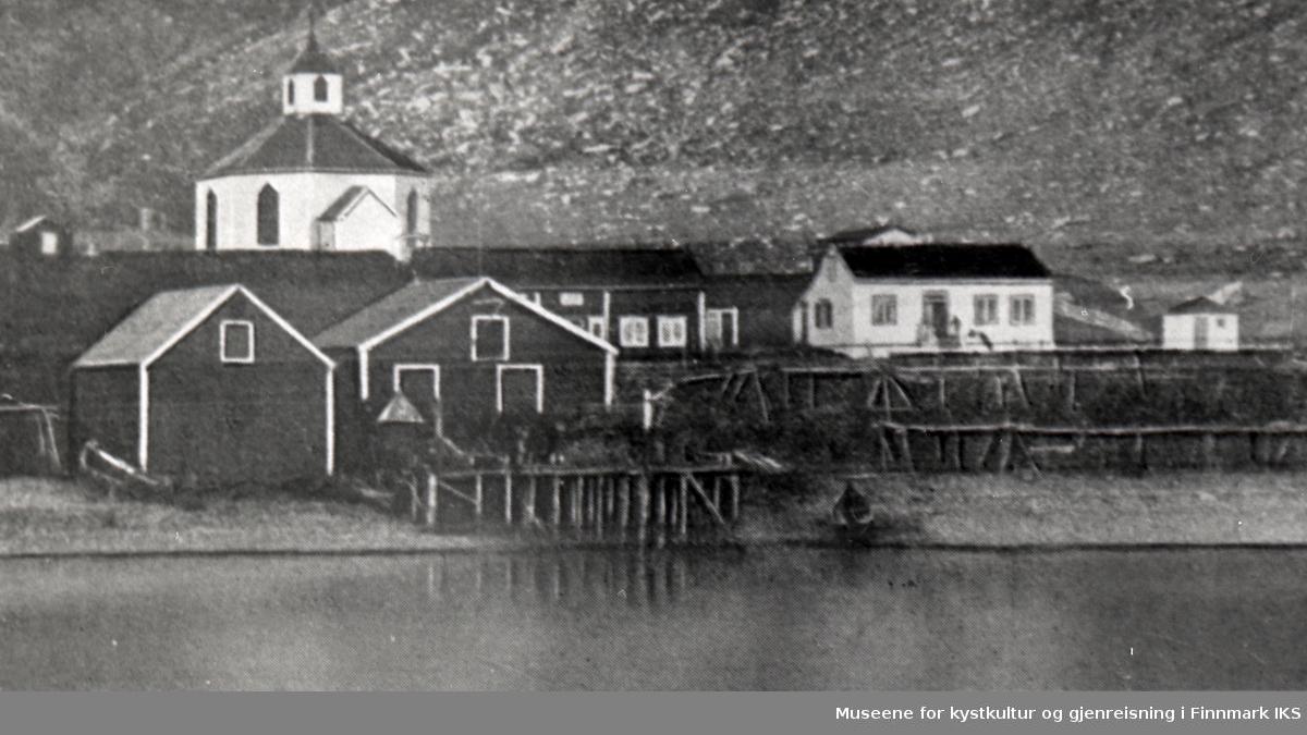 Handelstedet Kjelvik med kai, bolig, pakkehus og fiskehjeller. Kjelviks gamle åttekantete kirke (1844-1882) i bakgrunnen. Før 1882.