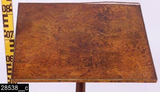 """Anmärkningar: Bord, Erik Malmberg, 1789-1807.  Kvadratisk bordsskiva med mässinglister i kanterna. Profilsvarvat ben. Tre S-formade fötter. Baktill finns en mycket svårtydbar (sliten) stämpel som lyder """"E MALMBERG / I KÖPING."""" (bild 28538__b). H:710 Br:450 Dj:450  Bordsskivan är fanerad med alrot, blindträet är furu. Alroten är fernissad. Benet och fötterna är av ljust, mörkbetsat lövträ Bild 28538__c visar närbild på bordsskivan.  Mälardalen och framför allt städerna Arboga, Köping, Kungsör och Eskilstuna var under 1700-talets senare hälft och början av 1800-talet centrum för tillverkning av alrotsfanerade möbler och föremål. Här tillverkades bl.a. fällbord, byråar och olika sorters askar. Föremålen såldes inte bara inom mälardalen utan även till Stockholm och till andra länder. Det främsta namnet inom alrotsföremålsproduktionen är Jacob Sjölin (1737-1785). Alroten togs inte från alens rötter utan från stamansvällningar vid rötterna. I synnerhet vid Mälarens stränder har tillgången på detta sorts virke varit god. På slottet förvaras en kortkatalog, upprättad av f.d. antikvarie Carin Thorsén. Den upptar över 300 alrotsföremål tillhörande museer, privatpersoner etc.  Erik Malmberg (1760-1807), mästare under hallrätten i Köping fr.o.m. 1789, fr.o.m. 1794 mästare i Köpings snickarämbete. 1794-1804 var han även ålderman i samma ämbete. Malmberg svor en lång ed vid sitt inträde i snickarämbetet, denna finns återgiven i Västmanlands fornminnesförenings årsskrift 1932. Gesäller hos Malmberg var bl.a. Carl Grandell, Anders Lindell och Johan Jakob Sjölin (Jacob Sjölins son), samtliga senare mästare i Köpings snickarämbete. Då Åke Nisbeth skrev sin artikel fanns inga kända arbeten av Erik Malmberg.  Litteratur om alrotsföremål och snickare som är fanerade med alrot: Anette Glöde, Fanering med Alrot, Linköpings universitet/Carl Malmsten, 2001 Åke Nisbeth, Schatullmakare i Köping och Kungsör, Västmanlands fornminnesförenings årsskrift 1960 Torsten Sylvén, Mästarnas möbler : Sto"""