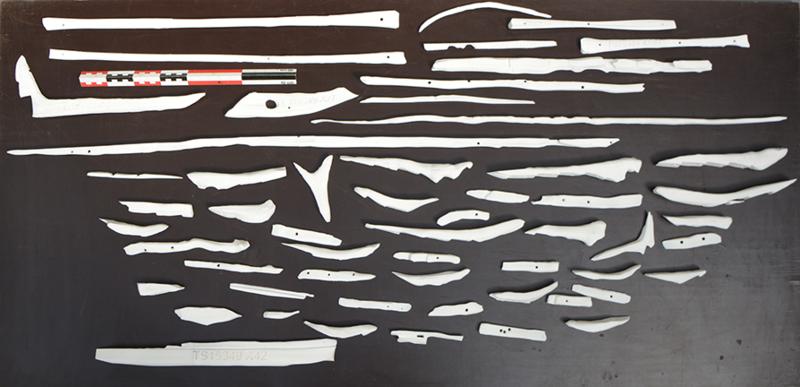 Oversiktsbilde av de 3D-printede delene til modellen av Lovundbåten. Små båtdeler i hvit plast ligger spredt ut på et bord.
