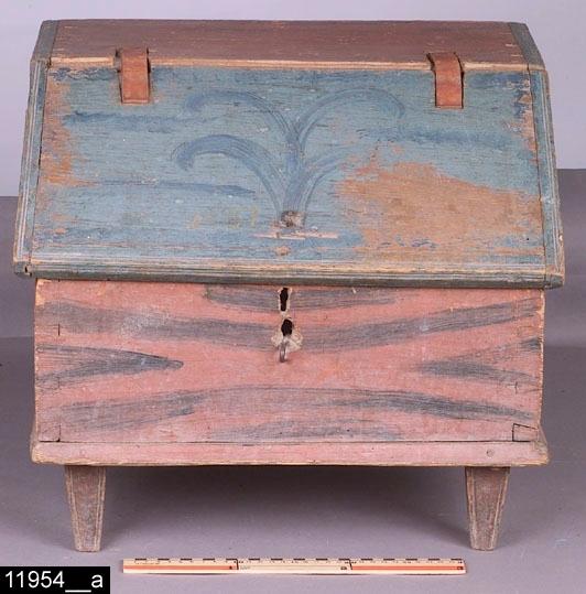 """Anmärkningar: Skrin, målad datering 1837.  Snedställt lock med räfflade kanter och en järnögla. På locket finns en målad datering """"1837"""" (bild 11954__b). Invändigt inrett med fem fack (bild 11954__c). Fyra nedåt avsmalnande ben med profilerade kanter. Locket är blåmålat med blå ådringsstreck. Övriga delar är brunmålade med bruna ådringsstreck. Färgen bär spår av naturligt slitage. H:415 B:470 Dj:395  Bild 11954__d visar skrinet från ena kortsidan.  Tillstånd: Lås och nyckel saknas. Gångjärnen saknas och är utbytta mot läderremmar.  Historik: Gåva från Herr Rutger Bergkvist, Karlfeldtsgatan 48, Västerås."""