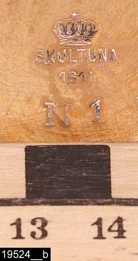 """Anmärkningar: Tekök, tvådelat, omkring 1900.  Löstagbar kanna med ett handtag av svarvat och svärtat trä. Lock med knopp. I botten av kannan finns stämplarna krona, SKULTUNA 1611 N1 (bild 19524__b). S-formad pip. Kannan står på två armar med genombrutna hjärtformade dekorer. Runt stativ med plats för brännare. Teköket finns avbildat och omnämnt i en priskurant från 1898. Den tillverkades i tre olika storlekar och kostade mellan 25-30 kronor. Den levererades med brännare (bild 19524__c). Enligt en broschyr, utgiven av museet 2007 och benämnd """"Skultunastämplar 1800-2000"""", användes den typ av stämpel som finns på föremålet mellan 1890-1922. H:280 D:210  Tillstånd: Nyskick. Brännare saknas.  Historik: Gåva av Länsmusei vänner 1977."""