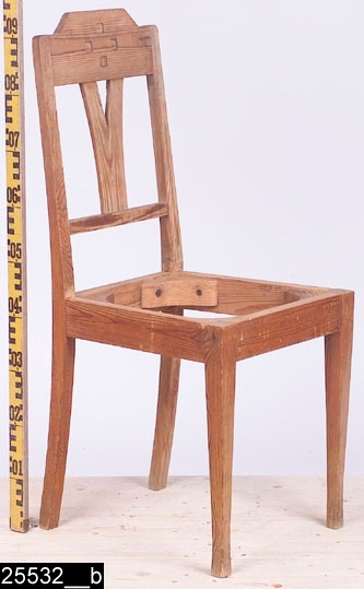 Anmärkningar: Stol, jugend, omkring 1910.  Överstycke med upphöjd mittdel och fyra kvadratiska urgröpningar. Svagt svängda bakstolpar (bild 25532__b). Genombruten rygg med en Y-formad ryggbricka. En ryggslå under ryggbrickan. Nedåt avsmalnande framben med något kraftigare fotavslutningar.  Tillstånd: Sits saknas.