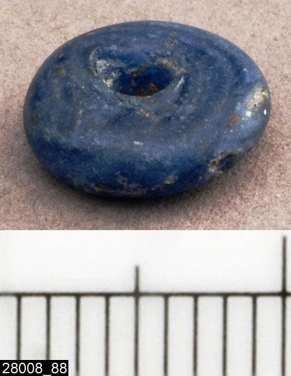 Anmärkningar: Badelunda sn, Tuna undersökt 1952-1953 Pärla, från båtgrav daterad till yngre järnålder, 850 e.Kr. (Vikingatid)  Pärla av glas, från grav 75 (fyndnr 88), 1 st, ringformig, liten blå. Diam ca 9 mm Utställd Forntid 2014  Pärlorna från grav 75 har omregistrerats av Access-projektet 2007 och då registrerats på enskilda poster under sitt ursprungliga (från rapporten) fyndnummer. De små vita, blå, gröna och bruna pärlorna som fanns i grav 75 har suttit i grupper om i allmänhet 2 eller 3 stycken mellan silverhängena.  Litteratur Nylén, E. & Schönbäck, B. 1994. Tuna i Badelunda. Guld kvinnor båtar I. Västerås kulturnämnds skriftserie 27. Västerås. s 44ff. Nylén, E. & Schönbäck, B. 1994. Tuna i Badelunda. Guld kvinnor båtar II. Västerås kulturnämnds skriftserie 30. Västerås. s 112 ff, 150ff, 200.  Fotograferad teckning negnr A-7422