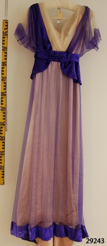 Anmärkningar: Irsta sn Geddeholm Använd av Ewa Lewenhaupt född Beck-Friis 1858 död 1940.  Flerfärgad lång klänning med släp. Innersta klänningen av ljust rosa siden. Upptill beigt tyll runt den djupt V-formade urringnningen och över axlarna. De korta ärmarna och resten av klänningen är täckt av lila tyll. Kring midjan ett brett bälte med skört av lila silkessammet, som går upp som ett band upp över högra axeln. Bak i ryggen finns bandet från vänster axel ner mot midjan, där de möts i korsryggen vid en stor lilafärgad sölja. Brett band av silkessammet kantar även den lila tyllen längst ner på klänningen. Klänningslivet fodrad med vitt bomullstyg, som knäpps med åtta knappar med hyskor i ryggen. Brett vitt band i midjan märkt Augusta Lundin Brunkebergstorg 20 Stockholm. Det yttre tyget knäpps tillsammans med den beiga tyllen överst knäpps med 20 hakar med hyskor i ryggen