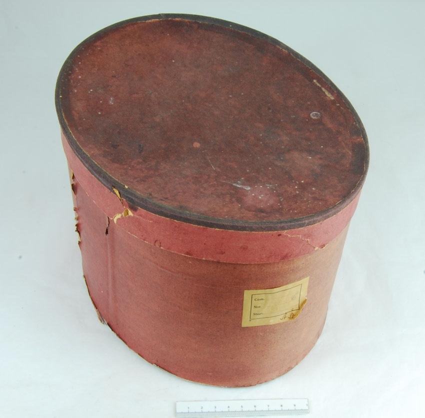Anmärkningar: Irsta sn Geddeholm  Bindmössa, 1 st, av rött bomullstyg mönstervävt med blommor i vitt, beigt, grönt, turkost, gult och svart. Inuti klädd med naturfärgat linne. Mössan saknar stycke. Tillhör folkdräkt. Förvaras i hög oval brun låda med lock. (Bindmössa, liten, styvad, rundkullig mössa, vanligen sidenklädd och broderad och ofta prydd med rosett baktill eller runt kullen. Den bärs högt uppe på kvinnans huvud och kompletteras av ett stärkt, spetsprytt s.k. stycke av lin. Källa NE)