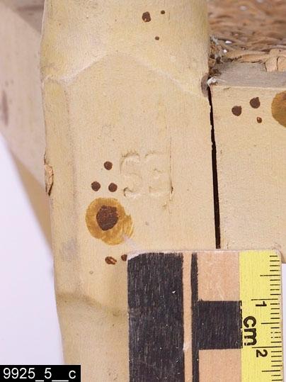 """Anmärkningar: Karmstol, av Ephraim Ståhl, omkring 1800.  Rakt överstycke. Svängda bakstolpar. Genombruten rygg med tre ryggspjälor och en ryggslå som ryggspjälorna är fästa i. På vardera sida finns ett armstöd som är fästa i bakstolparna. Armstöden är genombrutna och består av två vågräta spjälor och två lodräta spjälor samt en lodrät spjäla som sträcker sig ned till den översta benslån. Flätad rottingsits. I båda hörnen av baksargen finns Ephraim Ståhls signatur stämplad """"ES"""" (bild 9925_5__c, visar signaturen på den högra delen, signaturen är stämplad uppochned). Utåtsvängda bakben (bild 9925_5__b). Raka framben. En benslå mellan frambenen respektive bakbenen. Mellan frambenen och bakbenen finns på vardera sida två benslåar. H:865 Br:610 Dj:510  Hela stolen är svarvad (utom sargarna) och målad för att imitera bambu. Möblerna i serien 9925:1-12 söker imitera bambu. Sådana möbler har i omgångar varit populära i Sverige alltsedan kinasvärmeriet från mitten av 1700-talet till sekelskiftet 1800/1900. Enligt litteraturen på området tillverkades möblerna ofta för lusthus, en uppgift som också stöds av proveniensen från museets möbler - de har enligt liggaren stått i ett lusthus på herrgården Gideonsberg (riven på 1950-talet)! Invnr. 9925:1-6 är tillverkade av Ephraim Ståhl (1767-1820), mästare i Stockholms stolmakarämbete 1794-1820. Ståhl var den sengustavianska tidens kanske mest anlitade stolmakare, bl.a. hade han under några år inte mindre än åtta gesäller och tre lärlingar anställda. En omfattande produktion spreds till bl.a. departement, herrgårdar och slott.  Litteratur: Om Ephraim Ståhl se Eva Nordenfelt, Ephraim Ståhl : en kunglig stolmakare, 2007, s166-171. Några av museets möbler finns avbildade på s.168-169. Se även Torsten Sylvén, Stolens guldålder; stolar och stolmakare i Sverige 1650-1850, 2003, s203. Om bambumöbler se nämnda bok av Nordenfelt. Se även Britt Thunander, Illustrerat antiklexikon, 1986, uppslagsord Bambu samt Ingegerd Henschen och Sten Blomberg"""